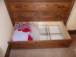 Window inserts are stored in a drawer next to sweaters.