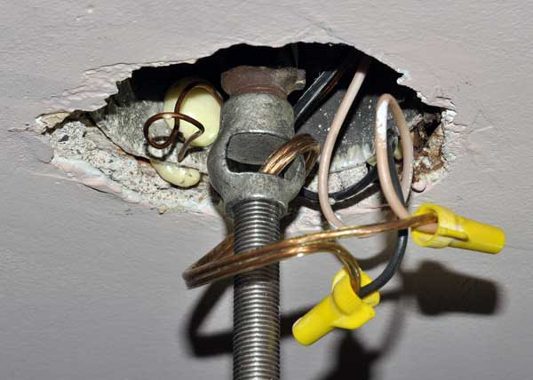 A light fixture connected to a ceiling electrical box using a hickey.