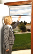 photo of retractable screen storm; woman lifting the panel.