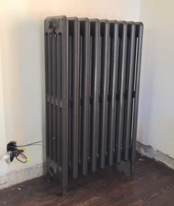This salvaged, refurbished radiator has been moved into place and is ready for installation.