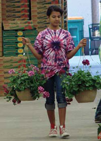 Photo of girl carrying hanging baskets.