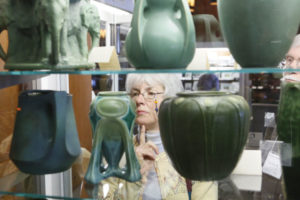 Woman viewing pottery.